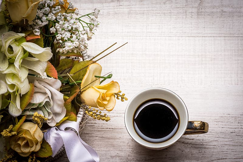 Cup with black liquid beside bouquet of flowers
