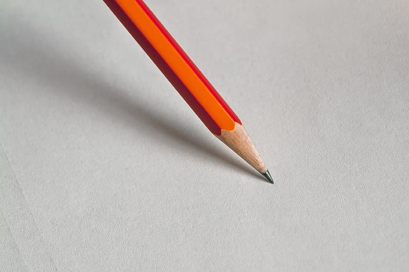 Orange pencil on white surface
