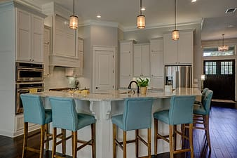 White sectional bar counter with bar chairs in kitchen