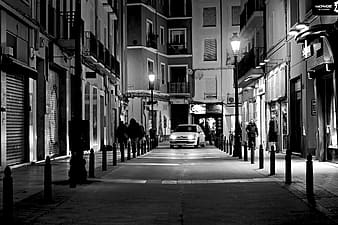 Grayscale photo of white car passing on isle surrounded buildings