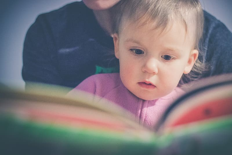 Baby in purple shirt reading book