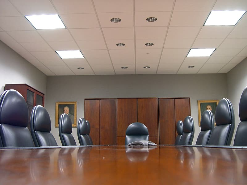 Brown wooden meeting office table and chairs set inside white room