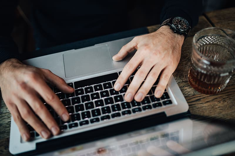 Person wearing black and silver watch using macbook pro