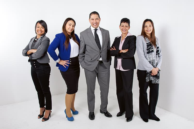 Five people in formal clothing standing near white wall