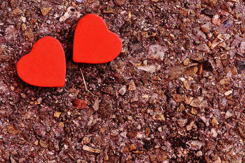 Two red heart decors on ground
