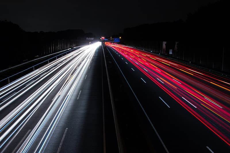 Time lapse photography of vehicle passing on road during nighttime