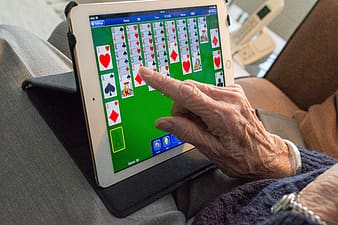 Person playing solitaire on white iPad