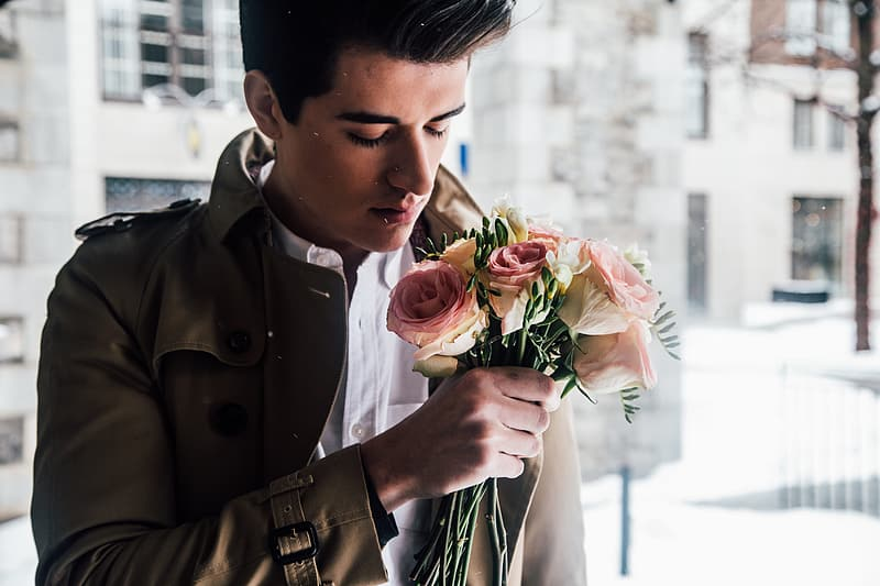 Man wearing brown jacket and white dress shirt holding white and pink rose