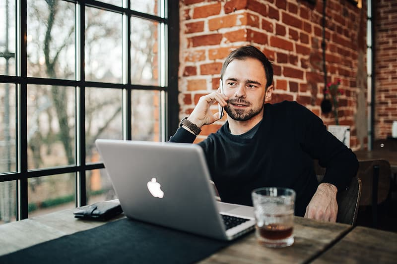Man in black sweater sitting in front of silver macbook