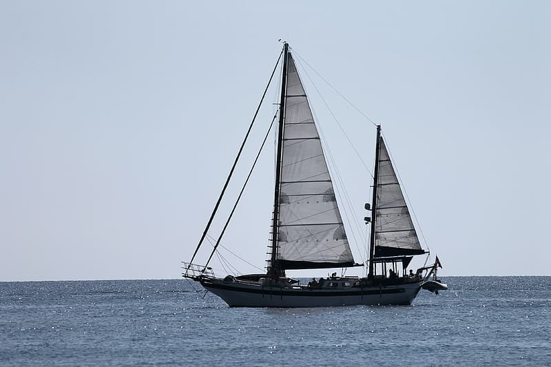 Black and white sail boat on sea during daytime