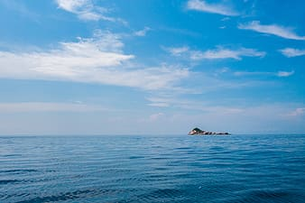 Brown rock formation on blue sea under blue and white cloudy sky during daytime