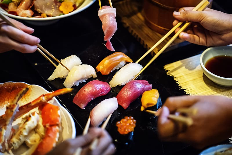 People getting sushi from grill