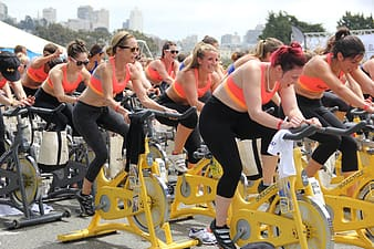 Time lapse photography of women riding stationary bikes
