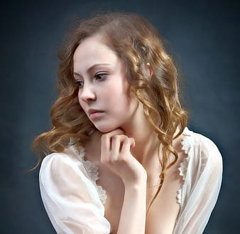 Woman in white top pose for photo while hand on her neck