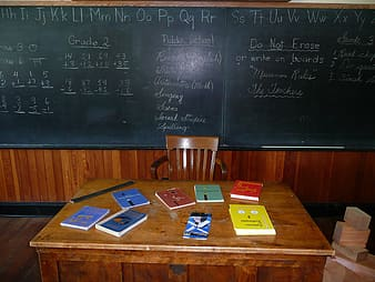 Titled book on table near a chalkboard
