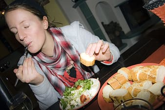 Girl in gray and red scarf eating
