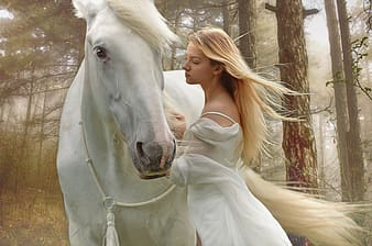 Woman in white dress standing beside white horse