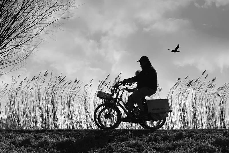 Man riding motorcycle in grayscale photography