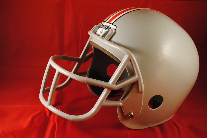 Gray and red football helmet on red textile
