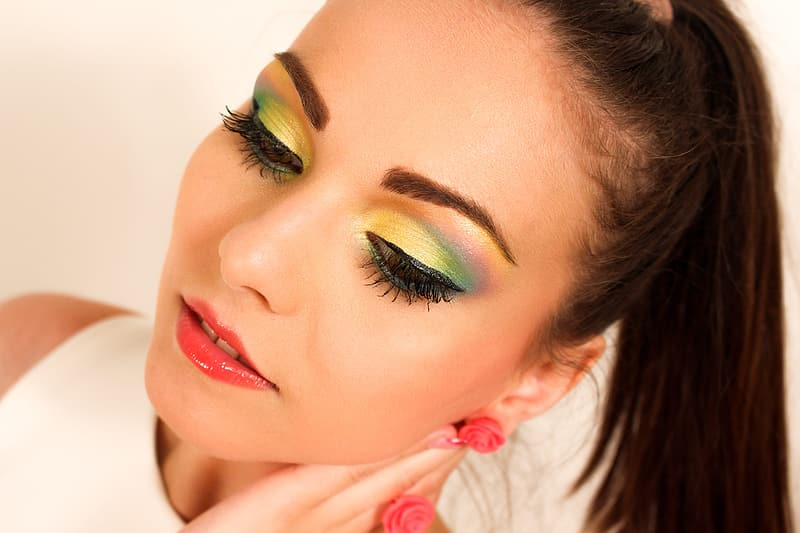 Photo of woman wearing white top with green eyeshadow and red lips