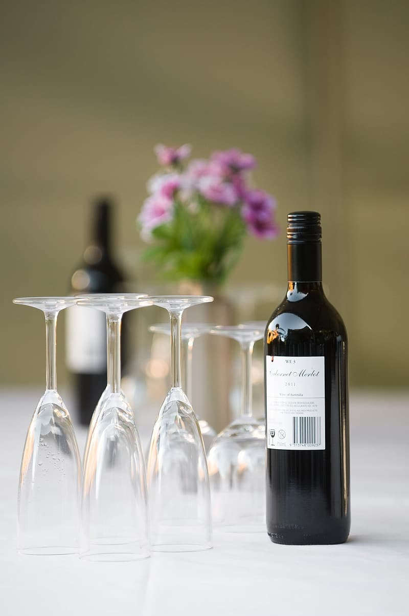 Selective focus photograph of wine bottle and glass on white surface