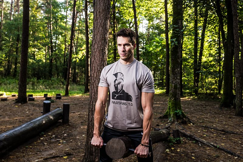 Man in black crew neck t-shirt standing on brown wooden log in forest during daytime