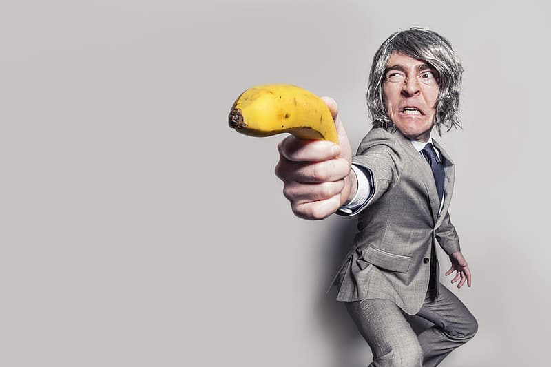 Person wearing suit holding banana near wall