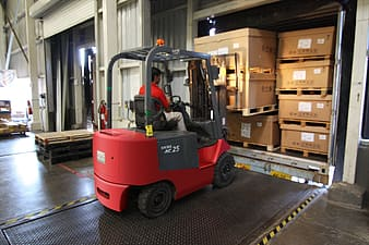 Man riding on red and gray forklift