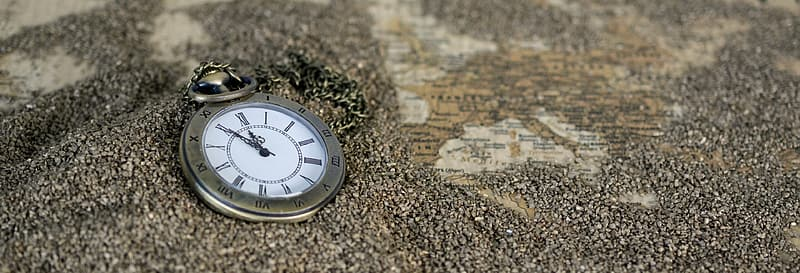 Round silver-colored pocket watch on brown sands