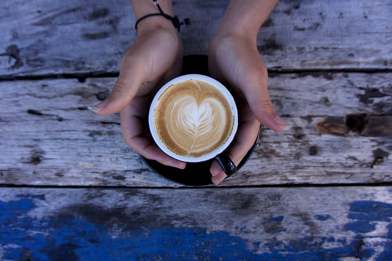 Person holding latte on black ceramic cup