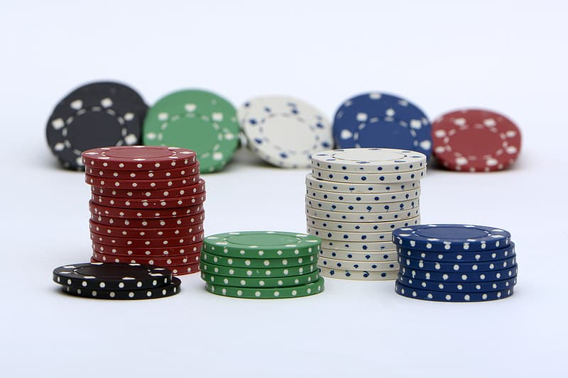 Assorted-color poker chips on white surface