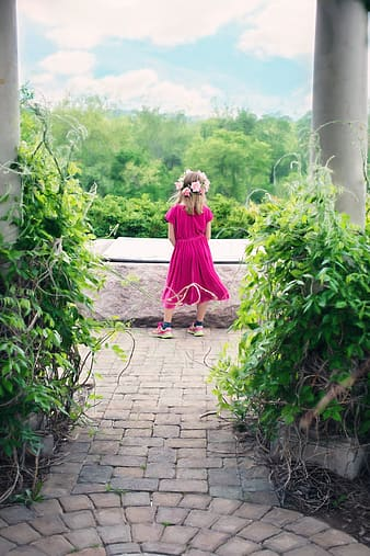 Girl wearing pink sleeved dress standing on pathway