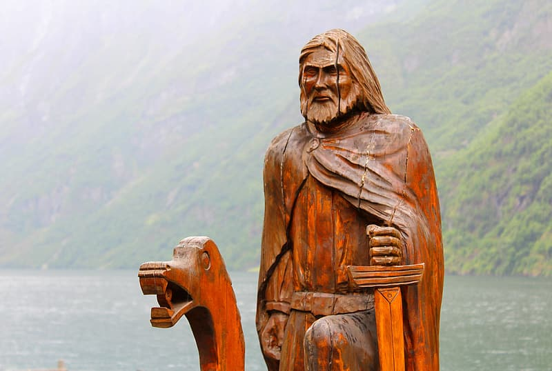 Brown wooden statue of man holding camera