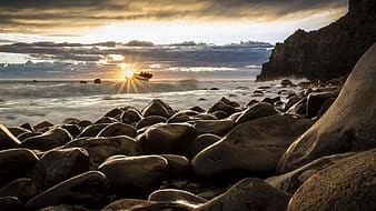 Pile of gray stones near sea during sunset