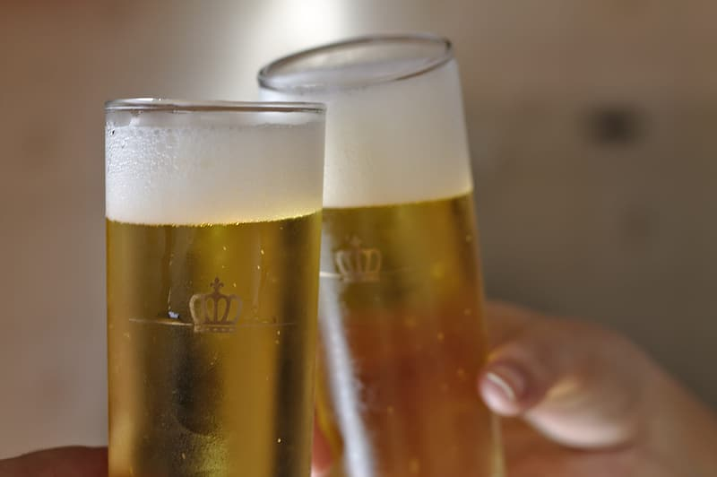 Person holding clear beer mugs