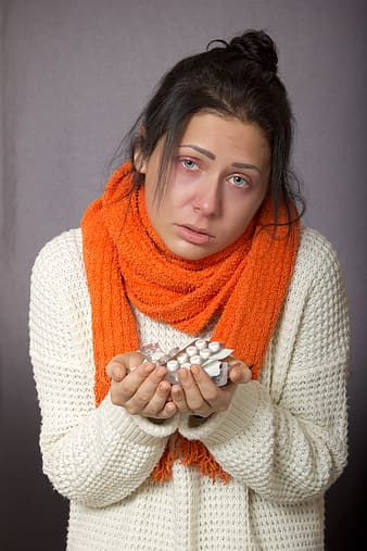 Woman wearing sweater and scarf holding medication tablets