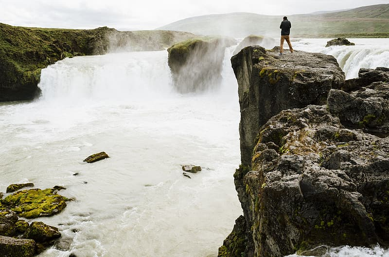 Person standing rock formation near body of water