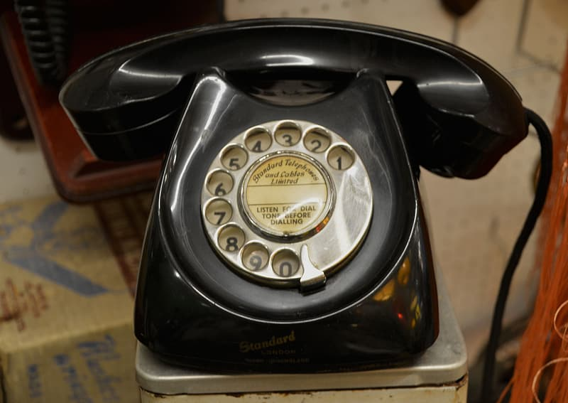 Black rotary phone in gray metal surface