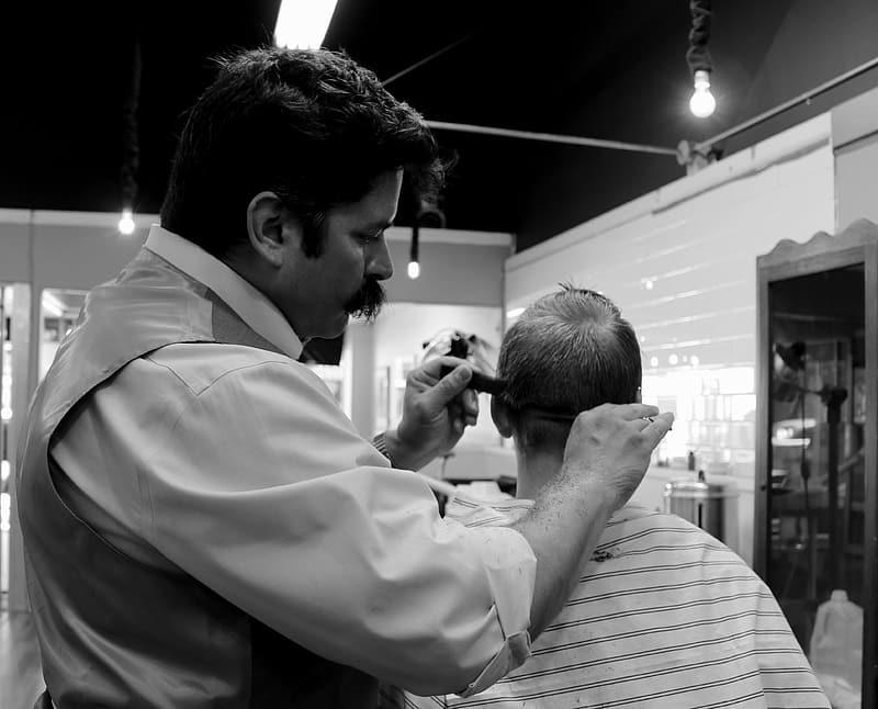 Grayscale photography of man doing haircut on boy
