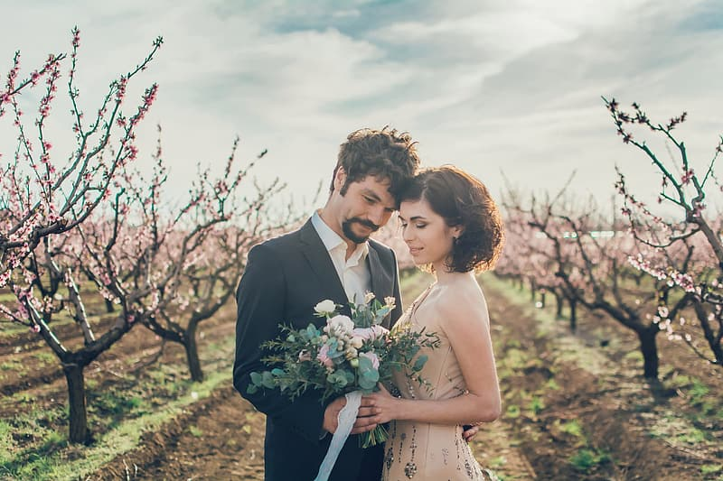 Man in black suit and woman in white dress holding bouquet of flowers