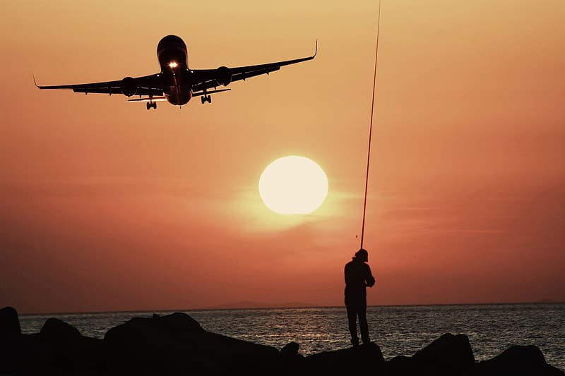 Person fishing under airliner during golden hour