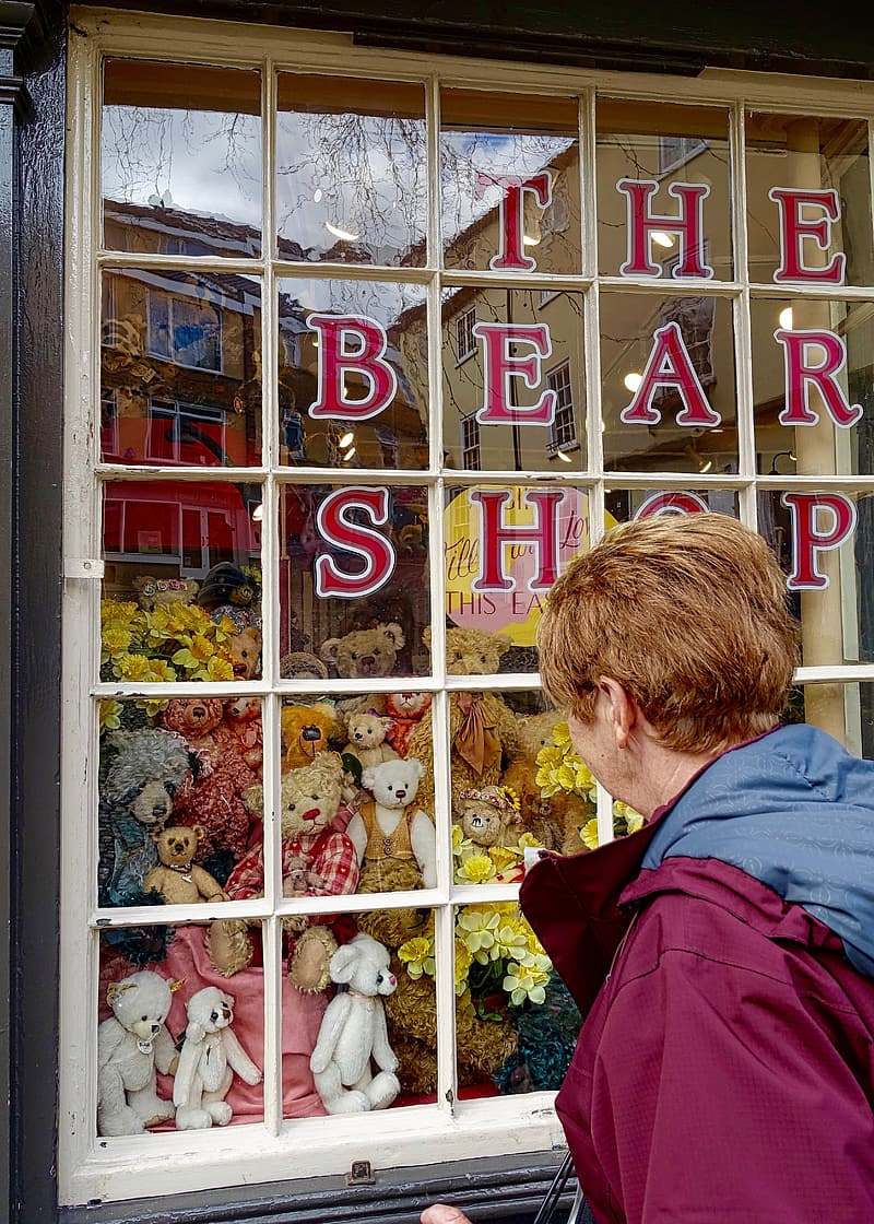 Man looking at window filled with plush toys