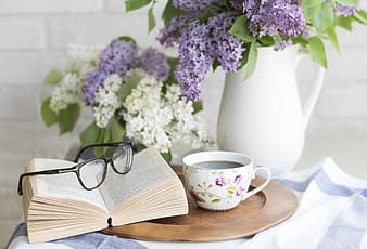 White open book with eyeglasses near teacup