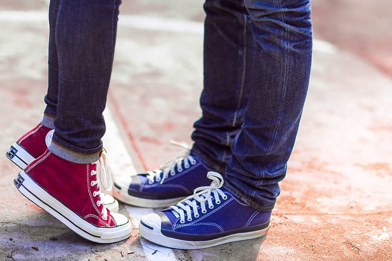 Two person wearing blue denim jeans, blue and red high-top sneakers standing