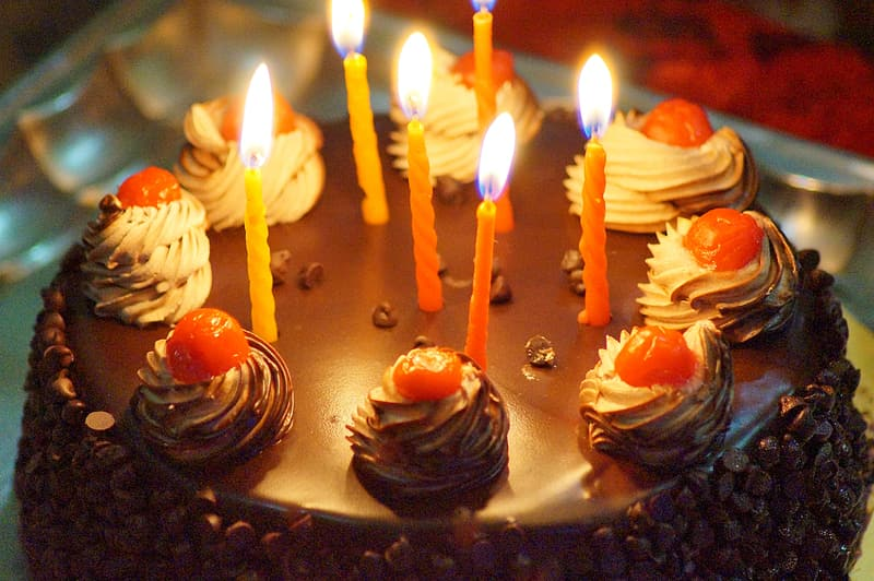 Close up photo of round chocolate cake with candles