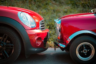 Closeup photography of red Mini Cooper and classic red Mini Cooper during daytime