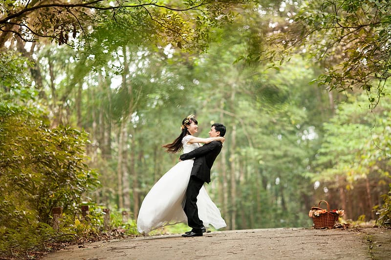 Selective focus photo of a groom carrying bride under green tall trees