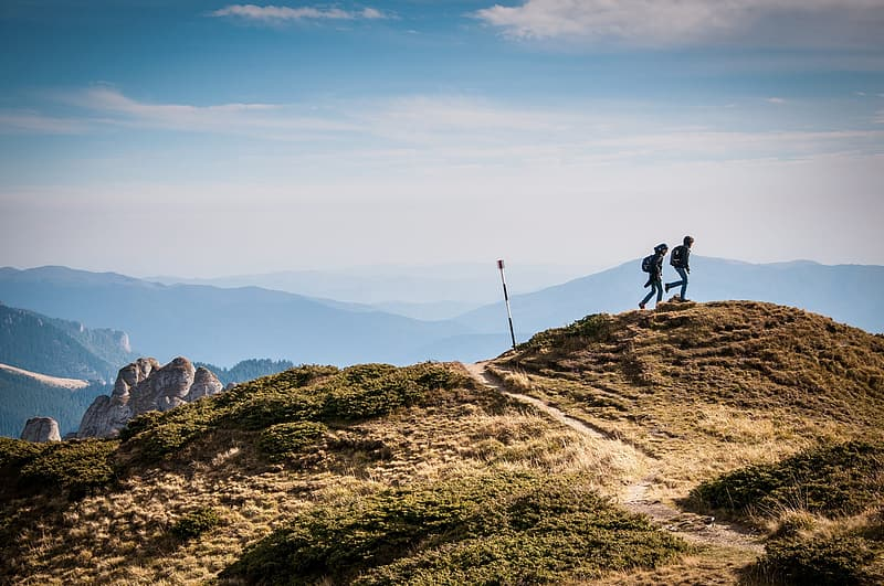 Two person on top of the Mountain seeing landmark under white cloud during daytime