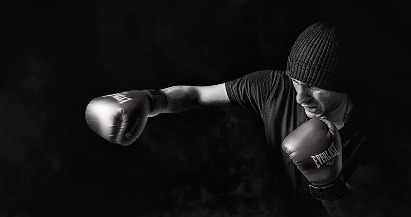 Grayscale photo of man wearing beanie and Everlast boxing gloves