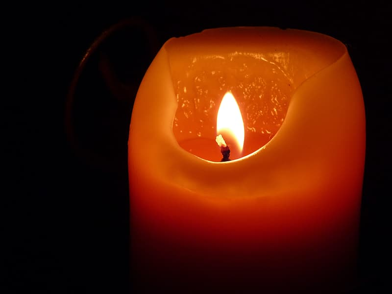 Red candle with fire in dark room